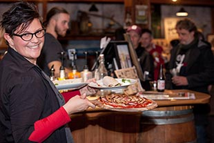 Waitress holding pizza